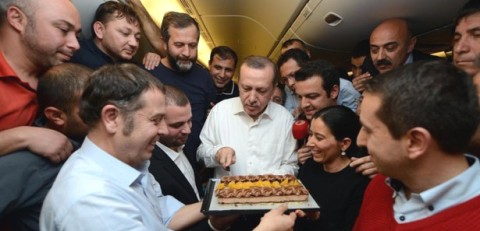 PM Erdoğan cuts a 'Journalists' Day' cake with Turkish reporters aboard his official jet in January. (Photo credit: Anadolu Ajansı)